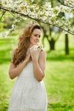 Bella giovane donna con capelli biondi in vestito bianco alla moda che posa vicino ad un albero di fioritura ad un giardino di fi fotografie stock libere da diritti