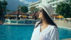 Bella giovane donna con capelli lunghi che cammina vicino alla piscina Turista al sole, vacanza archivi video