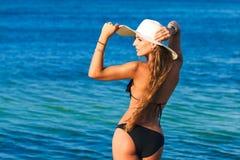 Bella giovane donna con capelli lunghi in un mare del cappello di paglia nella b fotografie stock libere da diritti