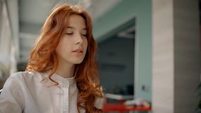 Bella giovane donna con capelli rossi in camicia bianca che si siede nel corridoio e nella conversazione dell'ufficio archivi video