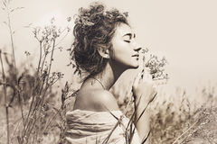 Bella giovane donna con gli occhi chiusi su un campo al tramonto Immagini Stock