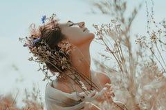 Bella giovane donna con gli occhi chiusi su un campo al tramonto Fotografia Stock Libera da Diritti