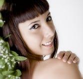 Bella giovane donna con i fiori in suoi capelli Fotografie Stock