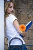 Bella giovane donna con i libri ed il fiore Fotografie Stock Libere da Diritti