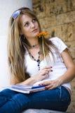 Bella giovane donna con i libri ed il fiore Immagine Stock