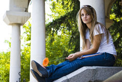 Bella giovane donna con i libri ed il fiore Immagini Stock