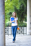 Bella giovane donna con i libri ed il fiore Fotografie Stock