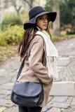 Bella giovane donna con il cappello nel parco di autunno fotografia stock libera da diritti