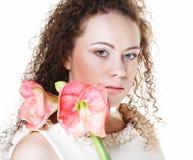 Bella giovane donna con il fiore rosa sopra fondo bianco immagine stock