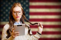 Bella giovane donna con il libro elettronico sulla bandiera di U.S.A. Fotografia Stock