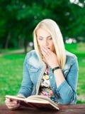 Bella giovane donna con il libro in parco immagini stock