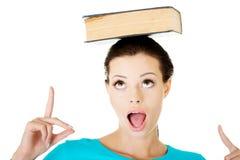 Bella giovane donna con il libro sulla sua testa. Fotografia Stock