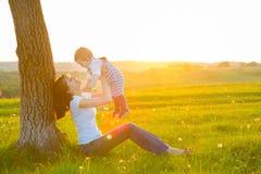 Bella giovane donna con il ragazzo sul prato della margherita Fotografia Stock
