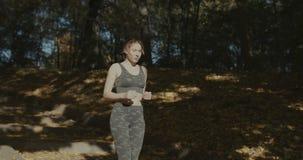 Bella giovane donna con il riproduttore mp3 che ascolta le arie ed il funzionamento nel parco della città archivi video