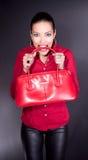 Bella giovane donna con il sacchetto rosso in denti Immagine Stock