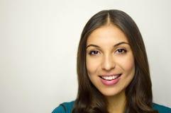 Bella giovane donna con il sorriso bianco perfetto con il copyspace grigio del fondo Fotografia Stock