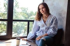 Bella giovane donna con il telefono cellulare e la tazza di caffè nell'interno domestico alla moda fotografie stock