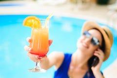 Bella giovane donna con il telefono vicino alla piscina immagine stock
