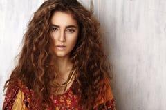 Bella giovane donna con l'acconciatura riccia lunga, gioielli di modo con capelli castana Vestiti indiani di stile, vestito lungo fotografia stock libera da diritti