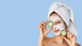 Bella giovane donna con la maschera facciale sul suo fronte che tiene le fette di cetriolo Cura di pelle e trattamento, stazione  immagine stock