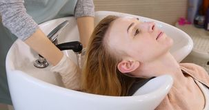 Bella giovane donna con la testa di lavaggio del parrucchiere al salone di capelli archivi video
