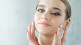 Bella giovane donna con pelle pulita e sana che posa sul fondo grigio stock footage