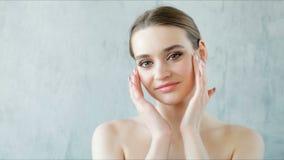 Bella giovane donna con pelle pulita e sana che posa sul fondo grigio archivi video