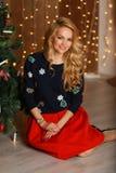 Bella giovane donna con trucco perfetto e capelli alla moda che si siedono sul pavimento vicino all'albero di Natale Immagine Stock