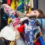 Bella giovane donna con un'bracciata dei vestiti in sue mani Immagine Stock