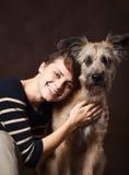 Bella giovane donna con un cane irsuto divertente su un backgrou scuro fotografia stock libera da diritti