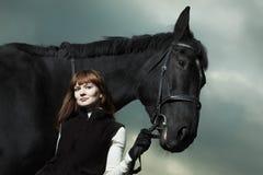 Bella giovane donna con un cavallo nero Fotografia Stock Libera da Diritti