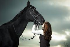 Bella giovane donna con un cavallo nero Fotografie Stock