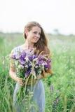 Bella giovane donna con un mazzo dei fiori sul prato di estate Fotografie Stock
