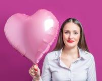 Bella giovane donna con un pallone a forma di del cuore su un fondo luminoso Concetto di giorno del ` s del biglietto di S fotografia stock libera da diritti