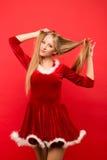 Bella giovane donna in costume di Santa che gioca con un mèche dei suoi capelli serici lunghi, esaminante macchina fotografica su Fotografie Stock
