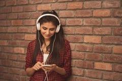 Bella giovane donna in cuffie che ascolta la musica sul fondo del mattone fotografia stock
