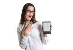 Bella giovane donna dai capelli lunghi allegra in vetri con un libro elettronico Immagini Stock Libere da Diritti