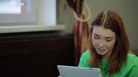 Bella, giovane, donna dai capelli rossi che tengono un computer della compressa, touch screen con le dita e sorrisi stock footage