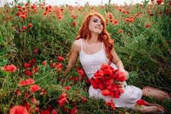 Bella giovane donna dai capelli rossi nel campo del papavero che tiene un mazzo dei papaveri immagini stock libere da diritti