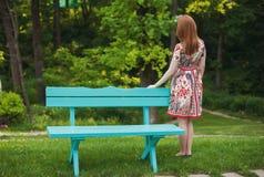Bella giovane donna dai capelli rossi in un vestito luminoso che sta indietro in natura, esaminante le finestre Fotografia Stock