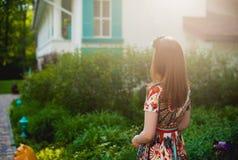 Bella giovane donna dai capelli rossi in un vestito luminoso che sta indietro in natura, esaminante le finestre Fotografia Stock Libera da Diritti