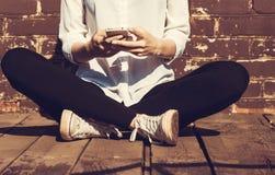 Bella giovane donna dei pantaloni a vita bassa che per mezzo dello Smart Phone fotografia stock libera da diritti
