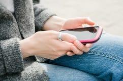 Bella giovane donna dei pantaloni a vita bassa che per mezzo dello Smart Phone rosa su un fondo grigio Fotografia Stock