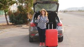 Bella giovane donna del viaggiatore con la valigia vicino al tronco di automobile stock footage