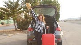 Bella giovane donna del viaggiatore con la valigia vicino al tronco di automobile video d archivio