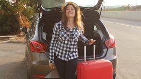 Bella giovane donna del viaggiatore con la valigia vicino al tronco di automobile archivi video