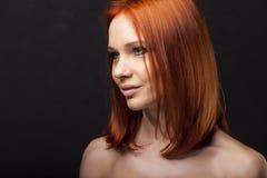 Bella giovane donna della testarossa con l'atteggiamento, forte ritratto su fondo scuro capelli sani diritti Immagini Stock