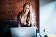 Bella giovane donna delle free lance che per mezzo del computer portatile che si siede alla tavola del caffè Ragazza sorridente f fotografia stock libera da diritti