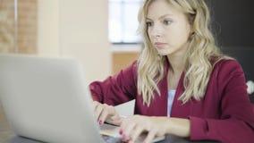 Bella giovane donna di affari bionda che scrive sul computer portatile sul lavoro stock footage