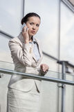 Bella giovane donna di affari che per mezzo dello Smart Phone all'inferriata dell'ufficio Fotografia Stock Libera da Diritti